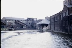 BW197-2-26-43-2 the Grand Union Canal at Paddington including a wide workboat and a butty moored near J Lyons factory, Paddington Basin and the wharf of W Boyer & Sons with wide boats moored