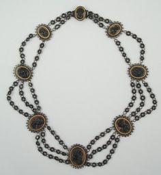 Berlin Iron Festoon Necklace with 8 Cameos Circa 1820s-1830s  The Neoclasical portraits on each medallion are silhouetted against a polished steel background.  Each steel plaque is rimmed with a gold bezel.  The clasp also has a cameo portrait.  The circles of iron-wire coils that  serve as the necklace chain were a common feature in jewelry and purses.