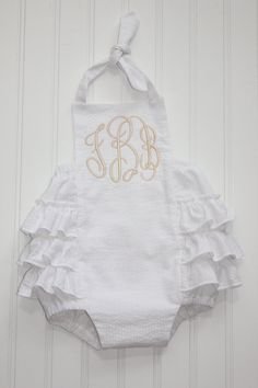 This sunsuit is so precious in person! Its made of white seersucker and has a light khaki monogram added. The back has 3 full rows of ruffles
