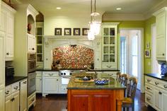 Large wood island.  Lime walls.  White kitchen.