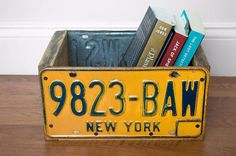 License plate book storage  If you have a small wooden storage bin that currently serves no purpose (and isn't pretty enough to use as is), cover it with old license plates for a quirky, yet simple makeover. It's the perfect size to store your favorite books!
