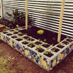 "Concrete Mosaic Planter: I like the pattern in the tiles repeated on the blocks. Usually, I don't like cinder block crafts. Kinda like repurposed tire stuff...""that's nice, but it still looks ugly."" On this, once the plants are big you wouldn't see it was made of cinder block."