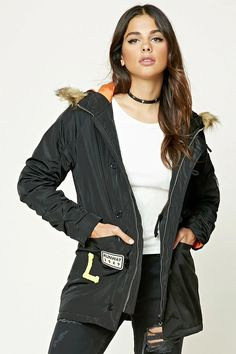 """A woven jacket featuring a faux-fur trimmed hood, various patches including a tiger, chevron and an """"L"""" patch, a button and zipper front, long sleeves, a zipper sleeve pocket, an interior drawstring waist, and a quilted interior."""