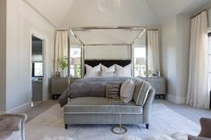 Stunning bedroom features a chrome canopy bed accented with a black velvet headboard dressed in white and gray border bedding  and a gray duvet flanked by gray cabinets as nightstands and white alabaster lamps placed below windows dressed in ivory curtains.
