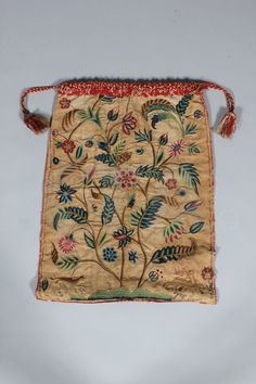 A crewel embroidered work bag, English, dated 1710, worked with a flowering plant sprouting from a hummock with small beasts running to either side, some of the blooms with French knot centres, edged in scarlet wool braid with tassels.