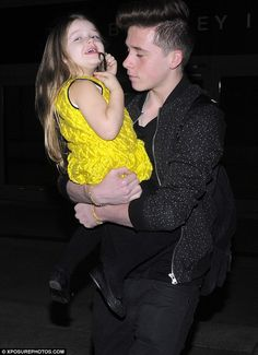 No sibling rivalry! Brooklyn Beckham carried his sister Harper through the terminal as the Beckham family - minus David - arrived at Los Angeles International Airport on Thursday