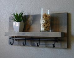Handmade entryway shelf mail organizer with satin nickel finish hooks. Perfect for any home entryway, apartment, or condo.  Made from solid wood. It has been lightly sanded down, then stained and sealed with a beautiful satin ebony finish.  This piece does not include the accessory items as shown in the pictures.  The color of the stained wood captured in the photos might vary slightly.  Dimensions: 23 in wide x 11 in tall x 4 in deep (pocket slot 1.5 in deep, top shelf 3.5 in deep x 21 in…