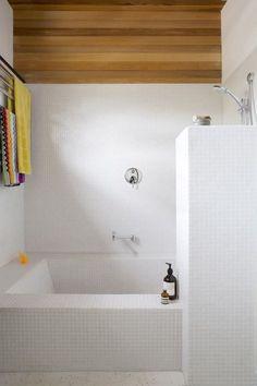 Dettaglio con vasca in muratura rivestita in mosaico bianco - parte del rivestimento e soffitto in legno che aggiunge un tocco di colore e originalità alla stanza