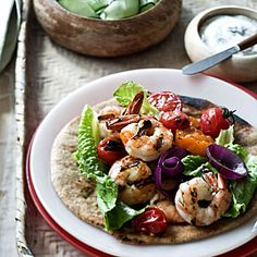 "8 Simple Summer Dinners    Grilled Shrimp ""Souvlaki""    This Greek dish combines seafood, veggies, and plenty of herbs for a delicious, fiber-packed Mediterranean meal.     Ingredients: Large shrimp, lemons, olive oil, dill, oregano, Greek yogurt, garlic, cucumber, pepper, cherry tomatoes, whole-grain flatbreads, red onion, romaine lettuce"