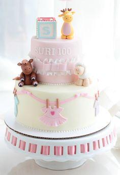 pastel de baby shower para niña de color rosa y blanco y decoraciones de osos y ropita