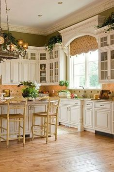 Ornate country kitchen with light hardwood flooring and recessed lighting.