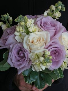 Soft and charming: cream stock flower, Vendella cream and Cool Water lavender roses with a small collar of variegated pitt. in this hand-tied bouquet.