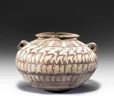Egyptian pottery jar, Predynastic Period, Naqada II, circa 3400-3300 B.C. Of ovoid form with flat rim and lug handles, decorated in red with hatched panels, a band of gazelles above a band of flamingos, with concentric rings around the base, 16 cm high. Private collection