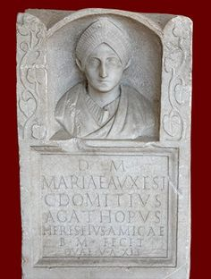 Funerary stele of Maria Auxesis; from the Via Labicana, Rome, Trajanic period (98-117 CE). The monument was dedicated by her friend and heir, Gaius Domitius Agathopus; he calls her his amica, a term usually indicating a mistress, though Maria Auxesis is portrayed in a severe style suitable for a married woman, with an elaborate hairstyle characteristic of the period.