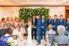 Indoor Ceremony in Ballroom Lobby with Flower Wall from Purple Magnolia | Rainy Charleston Wedding at The Dewberry Hotel by Charleston wedding photographer Dana Cubbage Weddings