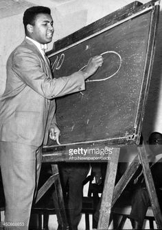 Boxer Muhammad Ali teaches a class by drawing on a chalkboard May 2 1964