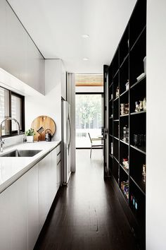 This modern pantry hides the fridge from the main living area. Dark built-in open shelving and additional cabinets provide ample storage.