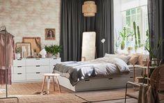 Hvit seng med skuffer i et stort soverom med mursteinsvegger, grå gardiner og jutetepper.