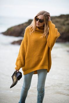 Mustard sweater, denim jeans. Latest fashion trends.