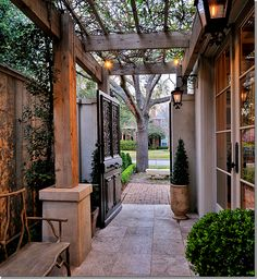 Zero lot lines.  VERY narrow spaces between houses.  You could build a pergola from your house – reaching almost to the brick wall.  This would leave space for a bed where you could plant vines and box.