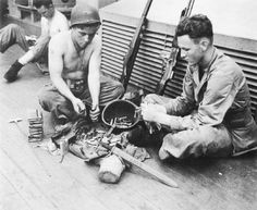 Marines (of the 2d Battalion, 2d Marines, 2d Marine Division) load up magazines and clean their weapons on board their attack transport Zeilin while en route to Tarawa.