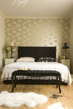 romantic bedroom with quilted bed and floral wallpaper, cole and son wallpaper, pink stylish armchair, pastel bedroom, oryginal bedside lamps, oak floor
