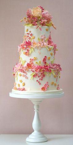Bolo de casamento de três andares cor menta com flores de açúcar comestíveis em rosa claro, amarelo, goiaba e folhas verdes.