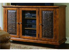 This plasma console features two outside doors with carved leather panels. It is crafted with hardwood solids and veneers with a distressed wood finish, carved leather, and nailhead trim.