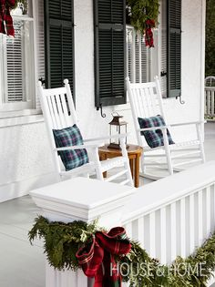 When cold weather hits, set up inviting seating on the porch as a place to relax with a steaming cup of tea. Bright-colored plaid throw cushions dress up these simple white rocking chairs.   Design: Christina Jeffrey   Photo: Donna Griffith