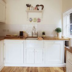 Small kitchen with white cabinetry, wooden flooring and wood worktop