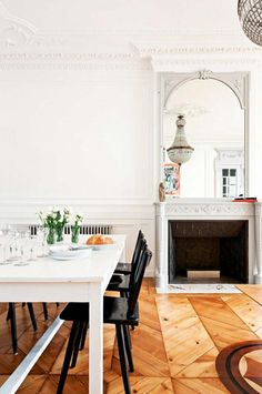 Decorative moldings on ceiling and walls of this all white dining space, featuring a fireplace, chandelier, and a white table with black chairs.