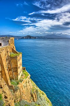 A cliff-side home of honey-toned rock looks out over an expanse of blue water. Procida, Italy. Photo by Maxime Bermond.