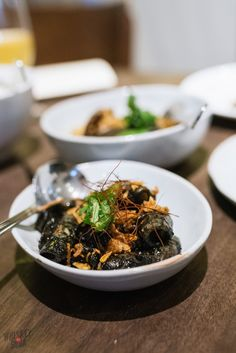 Wok-fried fresh squid with tamarind, chilies, and squid ink at Candlenut, Singapore