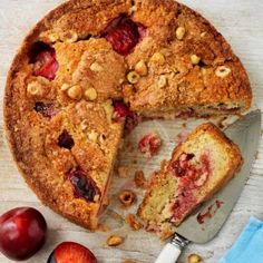 Plum and hazelnut cake with a large wedge removed. Plums and hazelnuts visible next to the cake