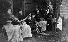 Making Music Margurett Powell Rider (violin) and Harriett Powell Myers (banjo) play for family members outside the George W. Powell home in Chestnut Flats. Photo taken around 1900