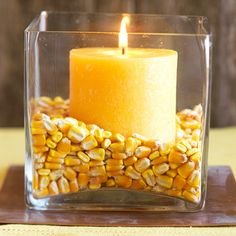 Creative Candle Idea  Nestle a candle into a vase filled with corn for a creative and quick fall centerpiece idea. Choose a theme and try other items such as jelly beans, buttons, or pennies. -- Also, a Vanilla candle nestled into coffee beans??