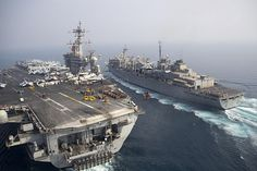 An MH-60S Sea Hawk helicopter assigned to the Sea Knights of Helicopter Sea Combat Squadron (HSC) 22 delivers cargo from the Military Sealift Command fast combat support ship USNS Arctic (T-AOE 8) to the flight deck of the aircraft carrier USS Theodore Roosevelt (CVN 71) during a vertical replenishment.
