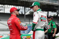 Justin Allgaier, driver of the No. 7 BRANDT Chevrolet, talks to Kevin Harvick, driver of the No. 88 Hunt Brothers Pizza Chevrolet, during qualifying for the NASCAR XFINITY Series Lilly Diabetes 250 at Indianapolis Motor Speedway on July 23, 2016 in Indianapolis, Indiana.