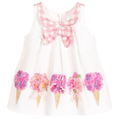 Baby girls white sleeveless dress byBalloon Chic. Made in smooth woven cotton with a pink floral print on the front and a pink and white check pattern on the back. Fastening with a concealed zip at the back, it has a Peter Pan collar with bow detail at the front, both in pink and white check. It comes with a pair of frilly knickers, also in pink and white check.