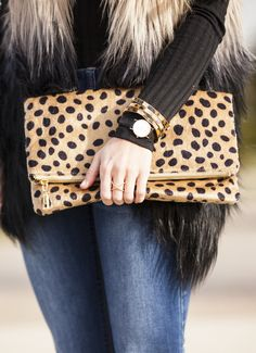 This is a MUST have Clutch and is PERFECT for every season. It is made from a Leopard Synthetic Fur Design. It features a foldover design, a detachable gold chain strap, one inside compartment and a z