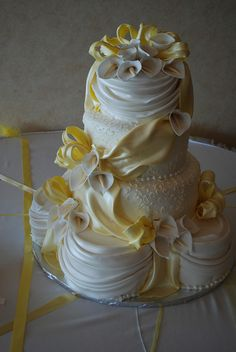 Very pretty cake with a lot of draping and beautiful yellow fondant ribbon and white calla lilies.  Beautiful.   ᘡղbᘡ