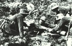 During the battle around Verdun in 1916, three German soldiers help a Frenchman out of the bottomless mud.