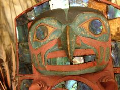 Tlingit headress, wood carved frontlet of a hawklike supernatural being that looks to be holding the cresent moon in eclips. Has the traditional black, red, blue green pains with abalone inlay. U Penn museum. via Tommy Joseph FB