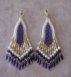 I had a hard time capturing the color purple in these earrings, they came out a little too blue. The top 2 photos on the mannequin head are the true depiction of the color purple.    These beautiful bead woven earrings are handmade with 12mm golden twist bugle beads, & purple rainbow, white luster, & golden glass seed beads, with 4mm white Czech glass pearls, 4mm purple Czech glass beads, & Czech glass daggers.    They measure just a touch under 3-3/4 long including the plated leverback…