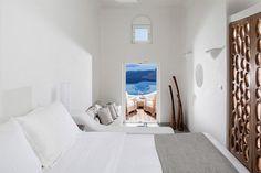 Imerovigli est connu pour être un village pittoresque sur la sublime île de Santorin et aussi une escapade de luxe. La preuve avec cette villa à flanc de falaise avec une vue imprenable sur la mer. Emprunt de l'architecture traditionnelle des Cyclades, la structure a été blanchie à la chaux et son intérieur s'apparente à une caverne grâce à des plafonds voûtés en dôme.