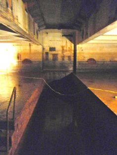 "Magazine B - View toward west of elevator machinery pit (54' x 9' and 6'4"" deep) below and underside of ground level elevator door opening above now sealed with concrete with  steel elevator doors removed."