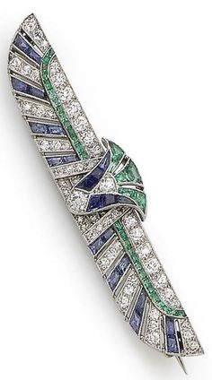 An Art Deco sapphire, emerald and diamond brooch, circa 1925. The pierced winged brooch set throughout with calibré-cut sapphires and emeralds and old brilliant and single-cut diamonds, diamonds approx. 1.00cts total, length 5.9cm, cased. #ArtDeco #brooch