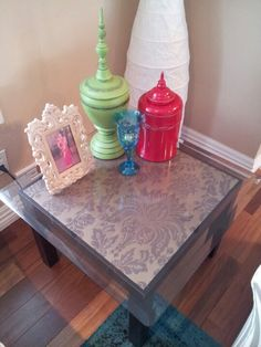 Upcycled an old and scratched Ikea Lack table into a pretty glass side table. Pasted leftover chocolate and bronze damask wallpaper and added a bevelled glass sheet on top.