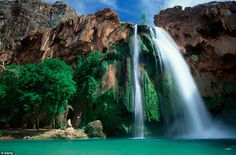 The Havasu Falls, located within Havasupai tribal lands, consists of cascading waters down the 100-ft vertical cliff into a large pool. Havasupai tribe lives in the village of Supai which can be visited by helicopter or mule, as it is eight miles from the nearest road hidden within the Grand Canyon...
