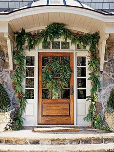 Ropes of garland made from magnolia, red cedar, winterberry, and pinecones complement the stone exterior of this Atlanta home.